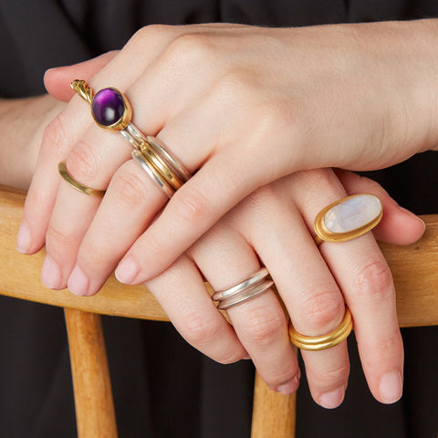 Silver, gold and amethyst ring with a selection of other silver and gold rings.