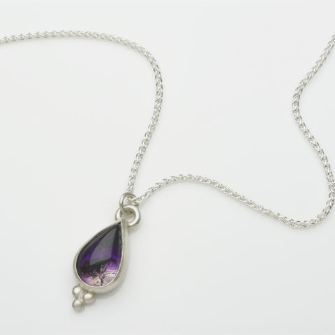 Pear shaped amethyst pendant set in silver with three orb detail.