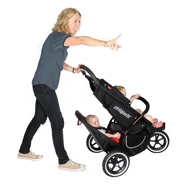 phil&teds classic buggy with mum pushing the buggy with double kit in lower position with child seated in both seats_black