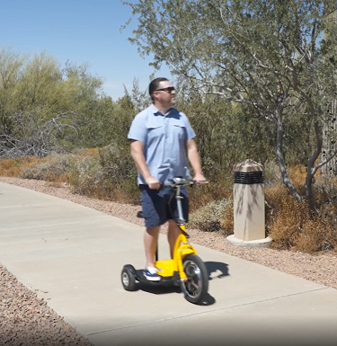 Image shows man standing on EWheels EW-18 electric tricycle scooter e-trike while riding on path