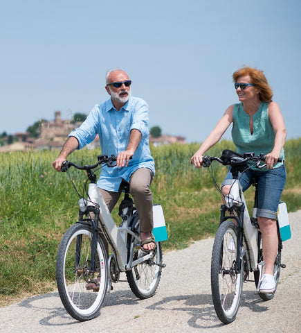 Two individuals riding on bicycles in the countryside