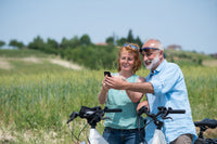 Image depicts couple taking a rest from riding electric cruiser bicycles in the country side
