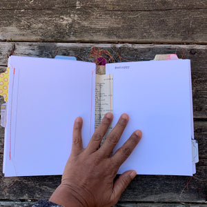 A hand holds down the middle  of a handmade journal that is sewn together and hand stitched in. Multi-coloured tab, excess thread from the sewing are visible. Paper looks textured.