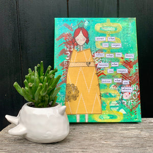 "mixed-media collage of girl in patterned yellow dress with turquoise green, yellow & red background. words are cut out and pasted on stating, ""attract what you expect, reflect what you desire, become what you respect, mirror what you admire"". Black background canvas sits on wood surface beside a plant for scale."