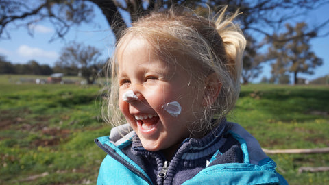 Laughing girl with lotion on nose and cheeks.