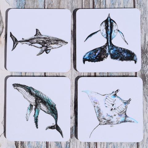 A set of 4 marine life coasters designed by Rachel Brooks Art- Each set includes a great white shark, humpback whale, manta ray and whale tail.