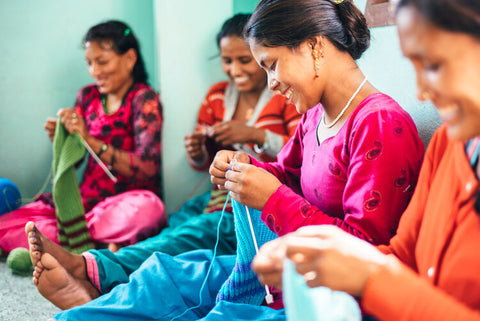 Happy women Smiling as they stitch clothing