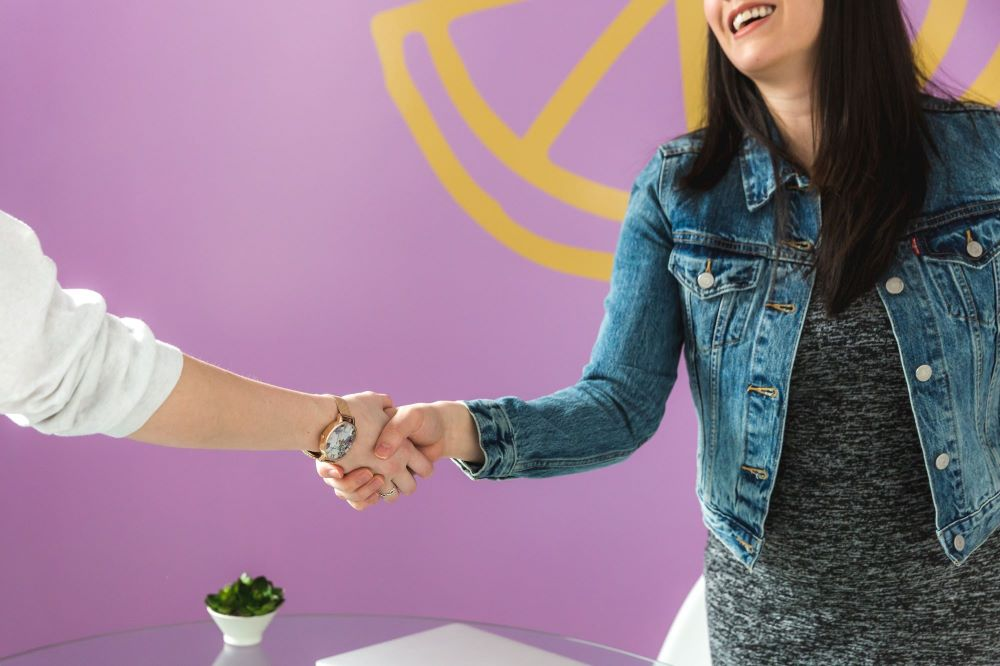 Happy woman hand shaking real estate agent