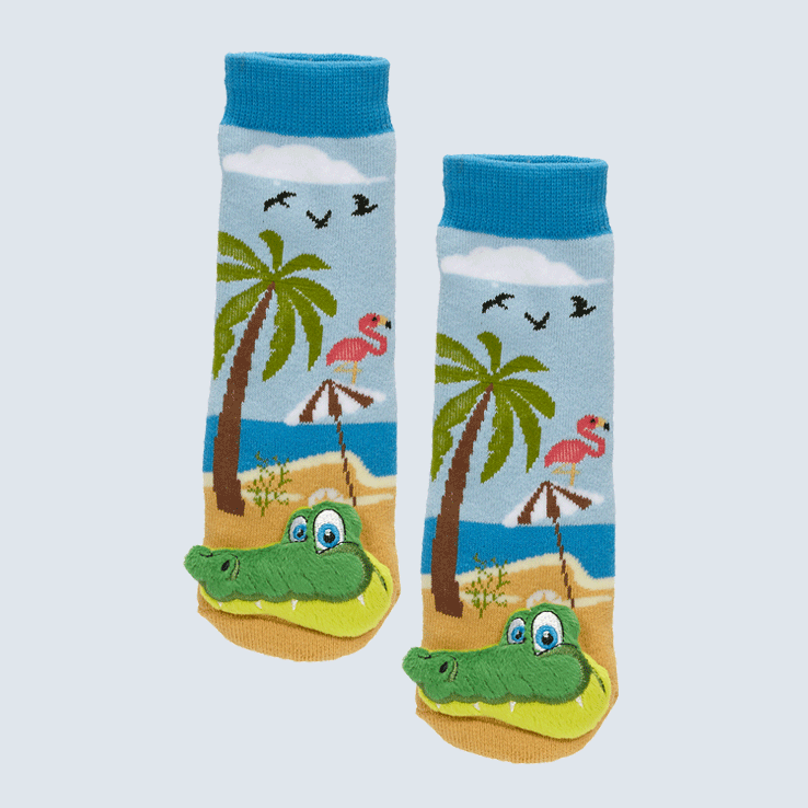 Two blue socks against a white background. The socks show a beach scene with a palm tree, flamingo, beach umbrella, and bird motifs. Each socks has an alligator charm on each toe.