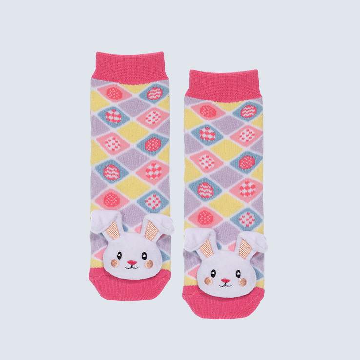 Two pink bunny socks against a white background. The socks feature pink, purple, blue, and yellow diamond motifs and a cute plush bunny charm on each toe.