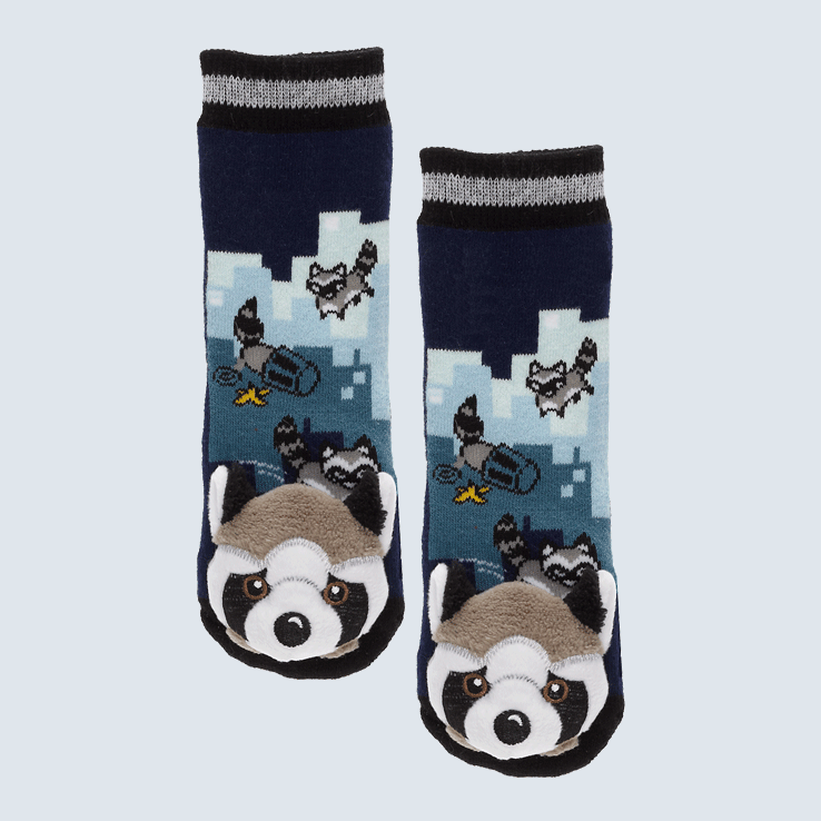 Two dark blue socks against a white background. The socks feature a raccoon and trash can motif and a cute plush raccoon charm on each toe.