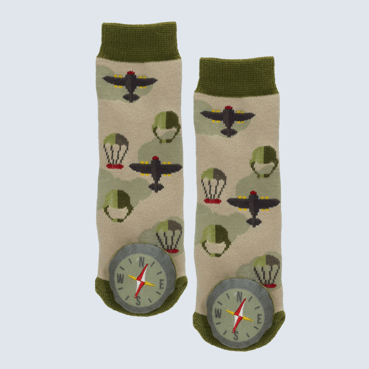 Two green and brown socks against a white background. The socks feature plane and parachute motifs and a plush compass charm on each toe.