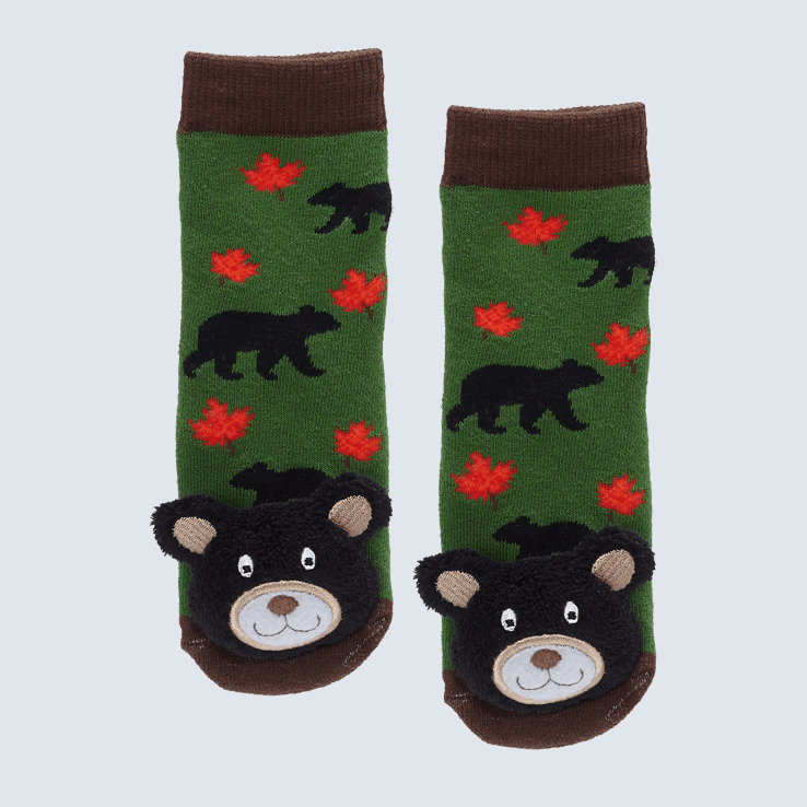 Two green and brown socks against a white background. The socks feature a red maple lead motif and a cute plush bear charm on the toe.