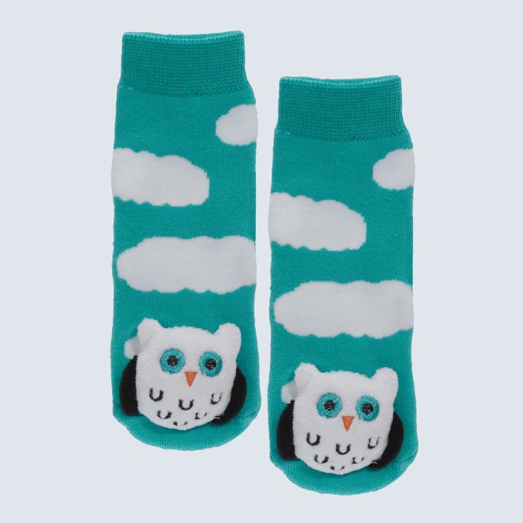Blue-green baby socks against a white background. The socks feature cloud motifs and a large owl plush on the toe.