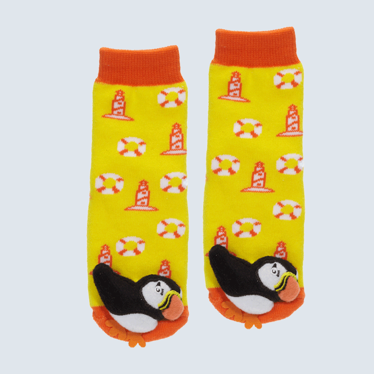 Two yellow and orange socks against a white background. The socks feature a lighthouse motif and a cute plush puffin charm on the toe.