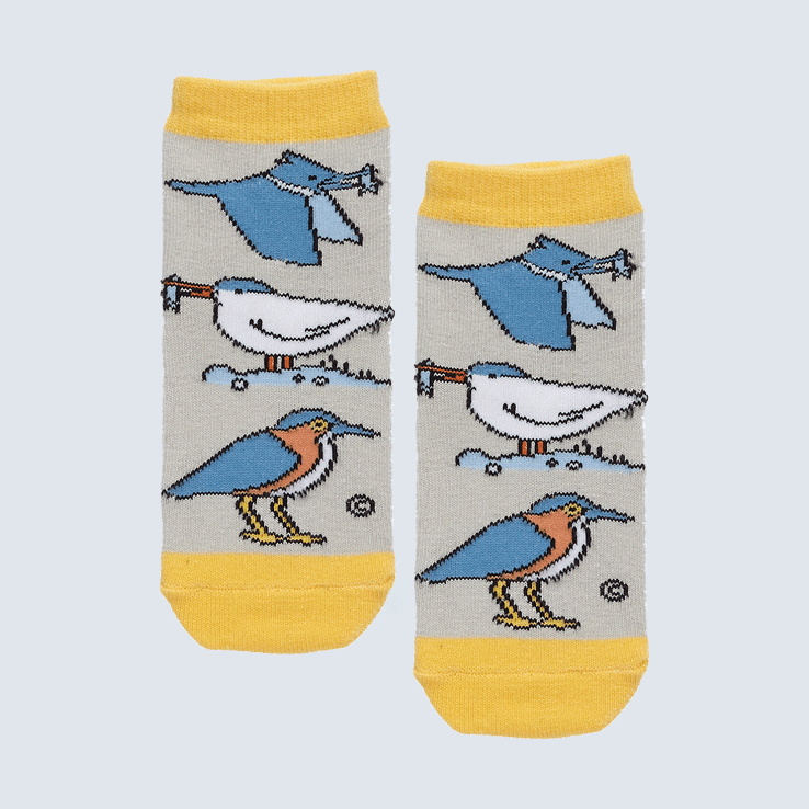 Two small socks against a white backdrop. The socks feature a gray and yellow and a motif with four sea birds.