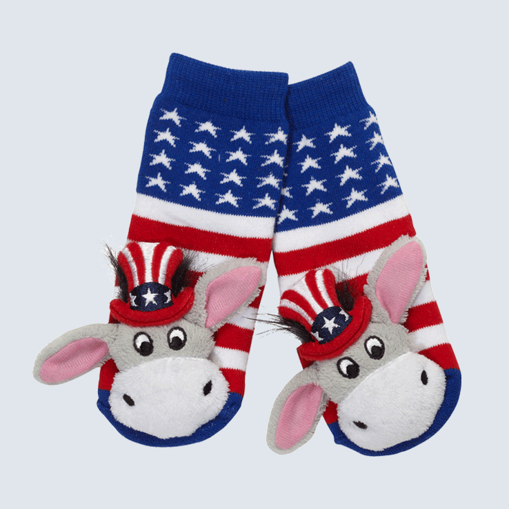 Two socks against a white background. The socks feature an American flag pattern and a cute plush donkey charm on the toe.