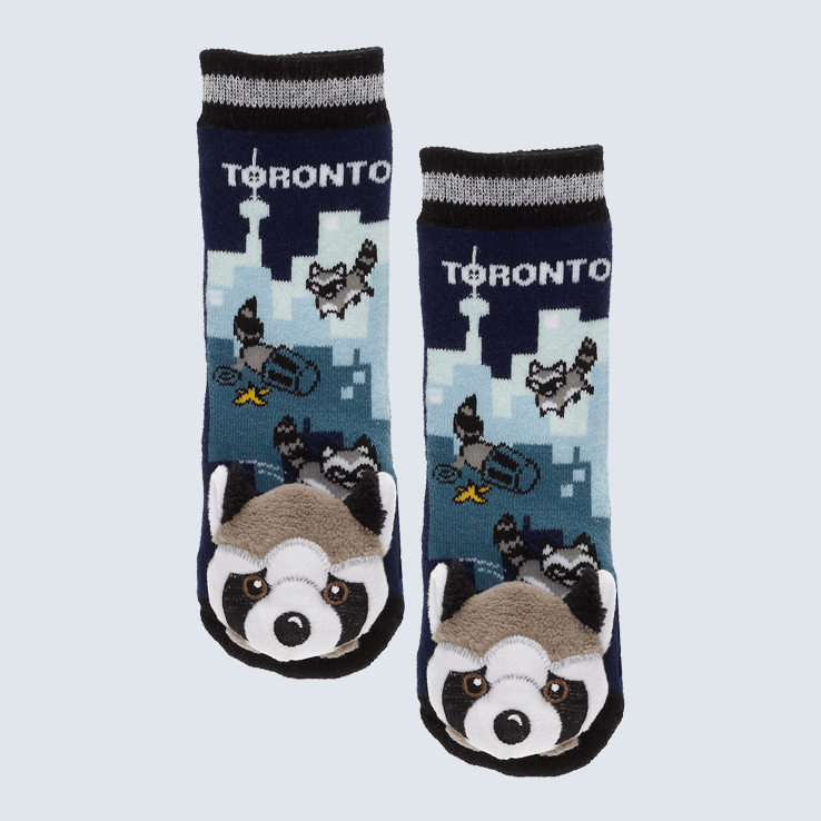 Two socks against a white background. The socks feature a Toronto skyline and a cute plush raccoon charm on the toe.