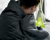 Man with Grey Blanket wrapped around his shoulders.