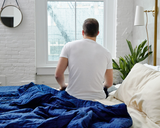 Man sitting up in bed, next to Navy Cooling Blanket