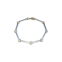 Load image into Gallery viewer, The Bar Bracelet sits as a strong statement piece on its own featuring 8 silver bars linked together with a hint of yellow gold. Handmade in Brighton by Scott Millar Jewellery.