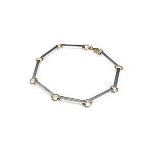 The Bar Bracelet sits as a strong statement piece on its own featuring 8 silver bars linked together with a hint of yellow gold. Handmade in Brighton by Scott Millar Jewellery.