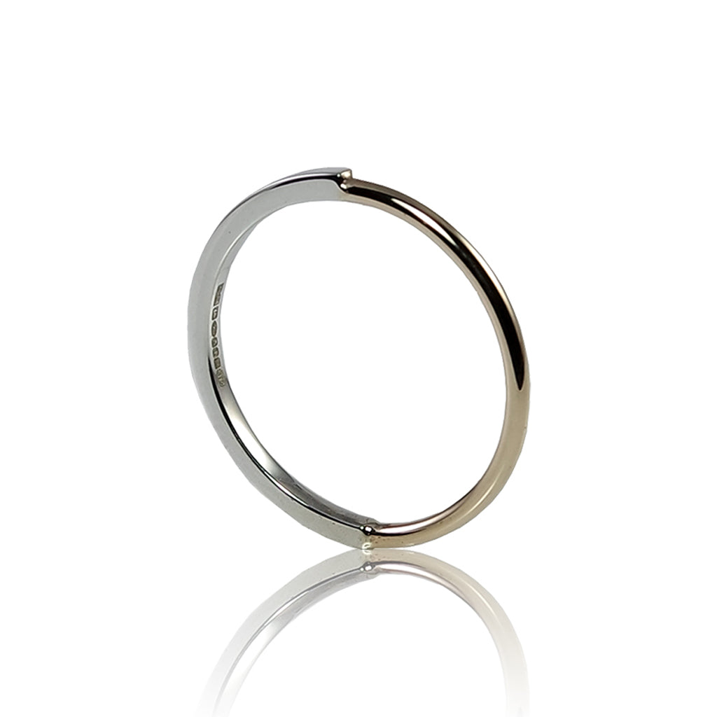 A silver and gold ring, half is a square silver profile, the other half a round gold profile. Finished with a high polish the silver and gold offer a striking contrast. Handmade in Brighton by Scott Millar Jewellery.