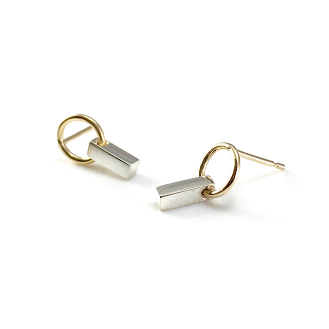 The Bar Earrings Mini feature a simple silver bar delicately suspended from a 9 carat yellow gold ring giving an eye catching movement. Sitting at 1.3cm in length, each silver bar is hand polished to a mirror finish to maximise the natural beauty of the material. Handmade in Brighton by Scott Millar Jewellery.