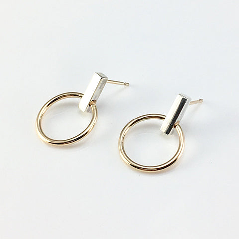 A mirror polished silver bar with a yellow gold circle suspended below. Earrings handmade in Brighton by Scott Millar Jewellery.