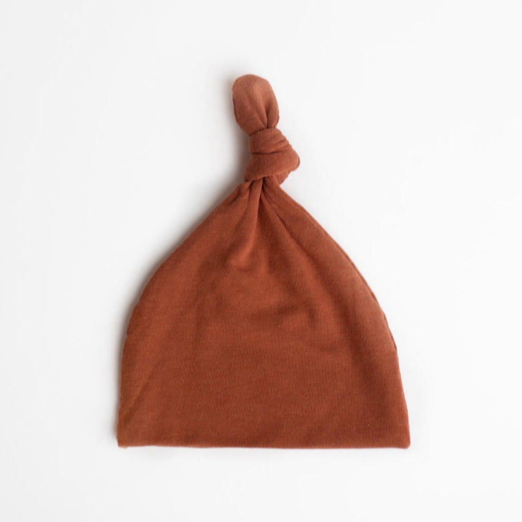 Top Knot Baby Hat in the colour Rust