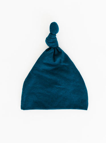 a full view of our Top Knot Hat for babies 0-3 months in Midnight Teal blue