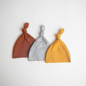 top knot baby hats in the colour rust, light grey and mustard