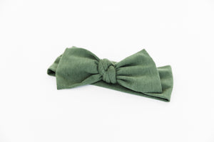 a close up view of our baby headband in moss green
