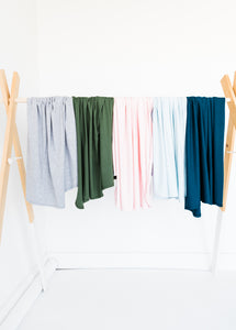 our collection of bamboo stretch swaddle blankets drapped side by side