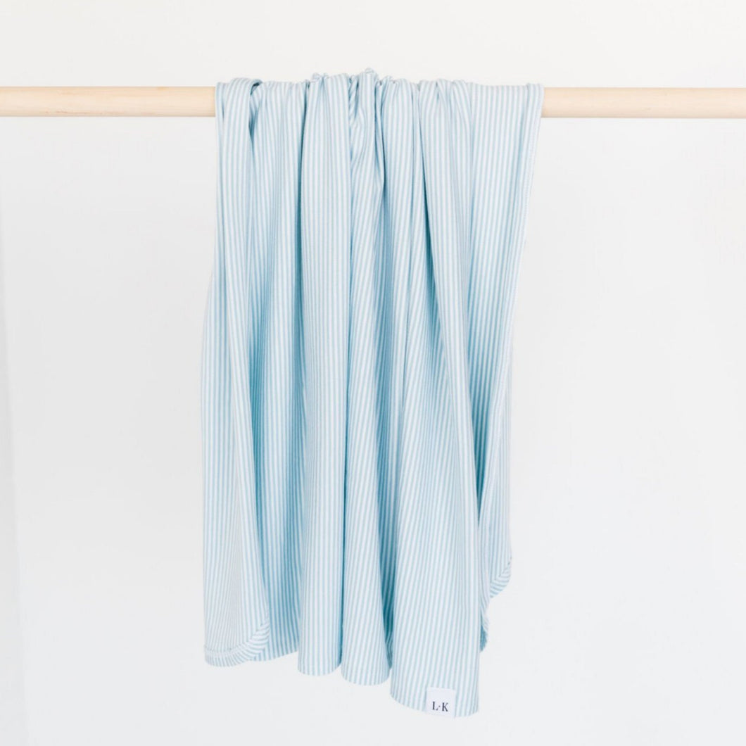 our bamboo stretch swaddle blanket in our baby blue stripe