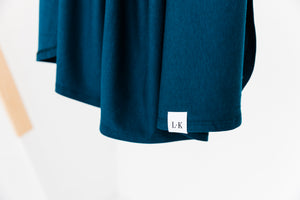 a close up of our branding tag on our Midnight Teal stretch swaddle blanket