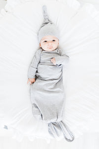 baby boy wearing our knotted baby gown in heathered grey and top knot hat in heathered grey