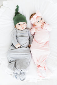 baby girl and boy laying side by side. Baby boy is wearing our knotted gown in light grey and top knot hat in moss green. baby girl is wearing our knotted gown in light pink and headband in light pink