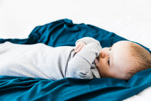 Load image into Gallery viewer, a baby boy cuddled on top of our midnight teal stretch swaddle blanket while wearing our knotted gown in heathered grey