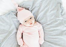 Load image into Gallery viewer, baby girl wearing our knotted baby gown and top knot hat in light pink paired with our heathered grey swaddle blanket