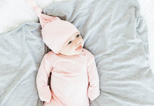 Load image into Gallery viewer, A baby girl wearing our Light Pink Top knot hat in size 0-3 months and our Light Pink knotted gown in 0-3 months. Her outfit is paired with our Heathered Grey Swaddle Blanket