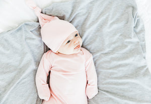 A baby girl wearing our Light Pink Top knot hat in size 0-3 months and our Light Pink knotted gown in 0-3 months. Her outfit is paired with our Heathered Grey Swaddle Blanket