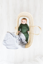 Load image into Gallery viewer, a baby boy in a bassinet wearing our moss green knotted gown with our heathered grey swaddle draped over the bottom of the bassinet