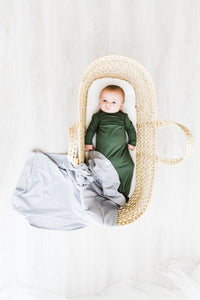 a baby boy in a bassinet wearing our moss green knotted gown with our heathered grey swaddle draped over the bottom of the bassinet