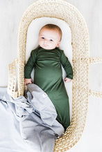 Load image into Gallery viewer, baby boy wearing our knotted baby gown in moss green paired with our heathered grey swaddle blanket
