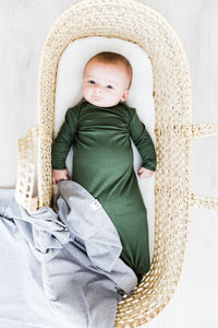 baby boy wearing our knotted baby gown in moss green paired with our heathered grey swaddle blanket