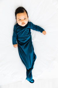 baby wearing our knotted baby gown in midnight teal
