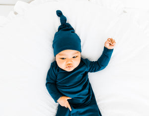 A baby boy wearing our Midnight Teal blue Top Knot hat and Knotted Gown both in sizes 0-3 months