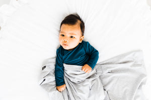 baby boy wearing our knotted baby gown in midnight teal and covered in our heathered grey stretch swaddle blanket