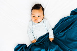 baby wearing our knotted gown in baby blue stripe paired with our swaddle blanket in midnight teal